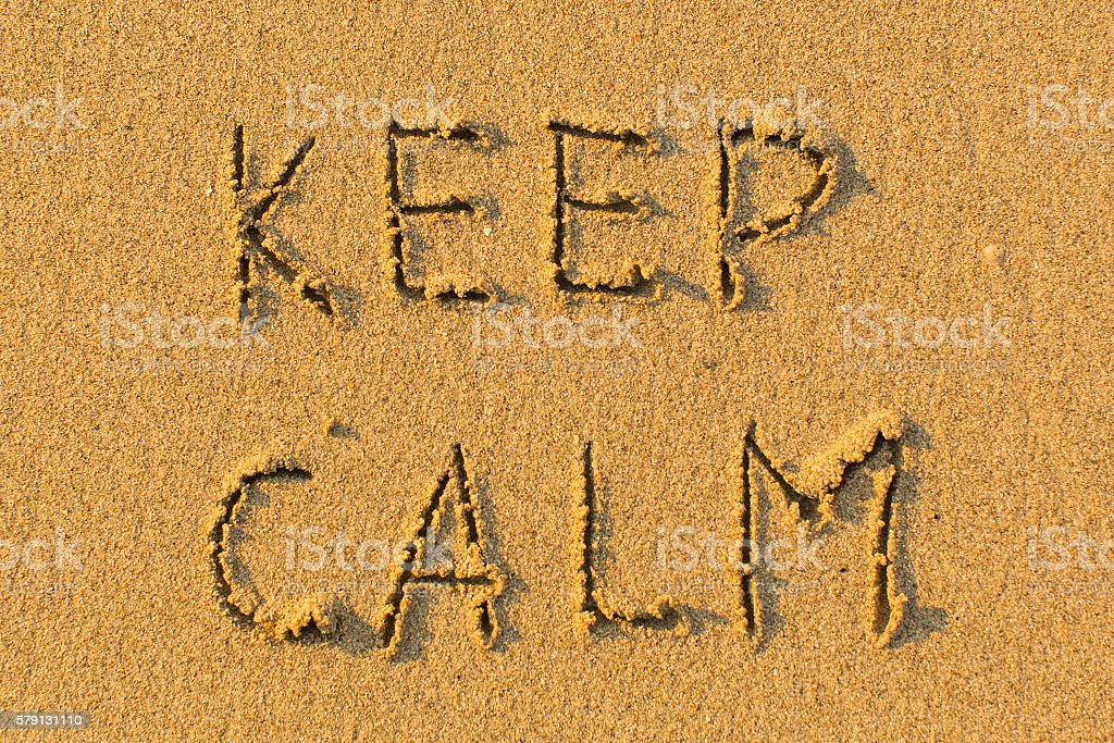 KEEP CALM - words hand-written on sand beach. stock photo