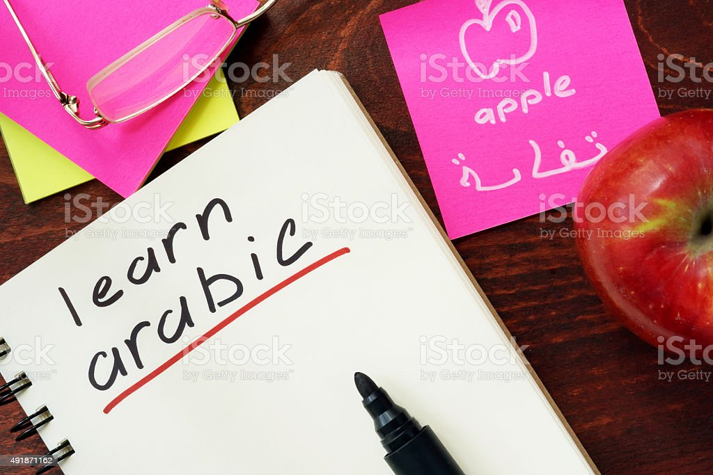 Words learn arabic written in the notepad. stock photo