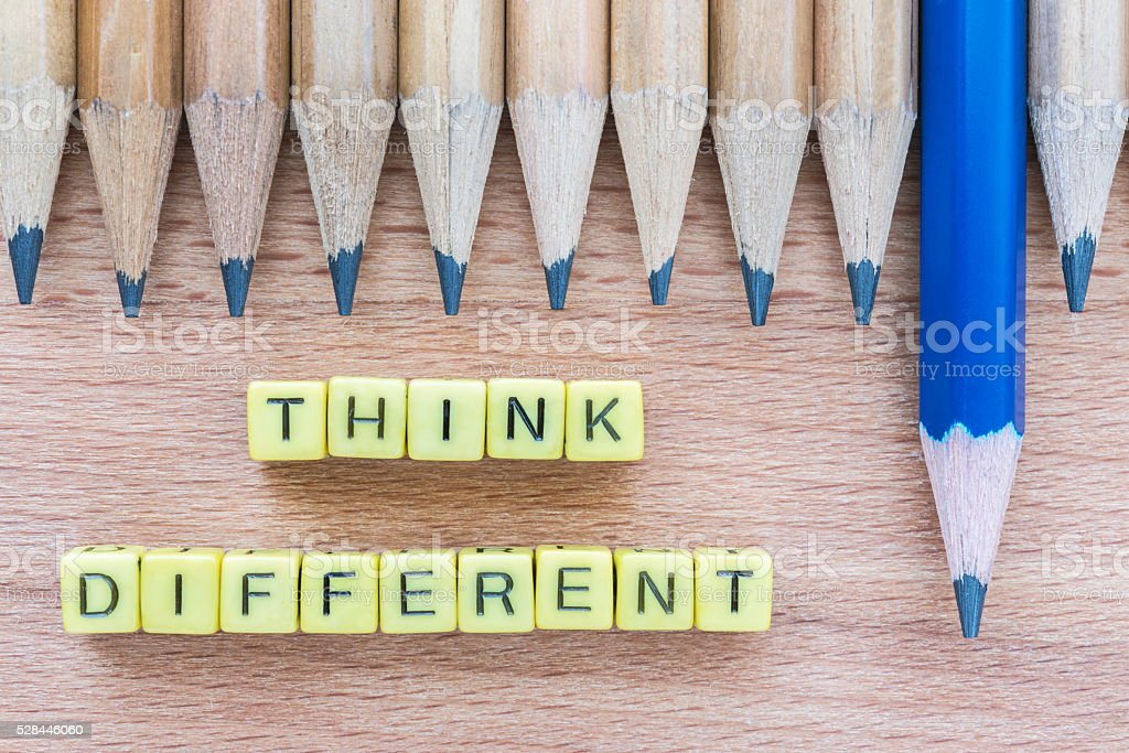 Words Think Different on wooden table with group of pencils stock photo