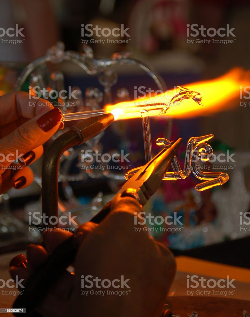 Woring with torch to shape glass into artistic forms stock photo