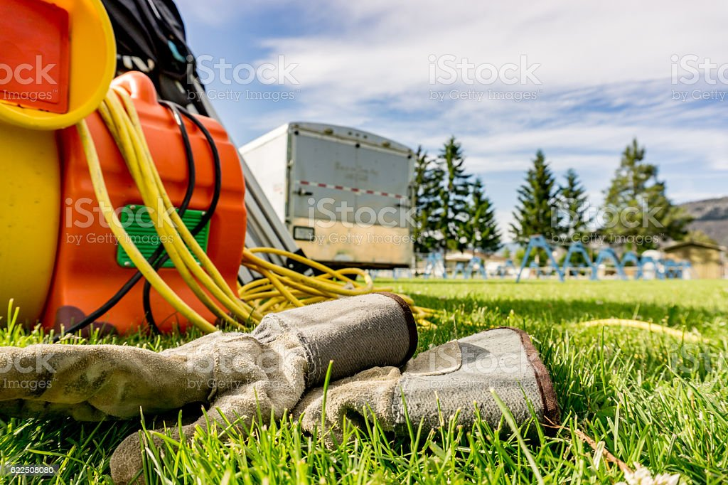 Work gloves and industrial fan on the grass stock photo