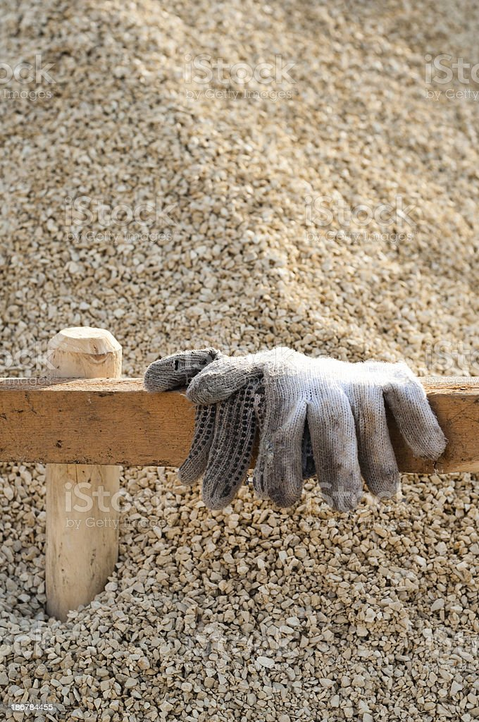 Work gloves on a board at crushed stones, construction site stock photo
