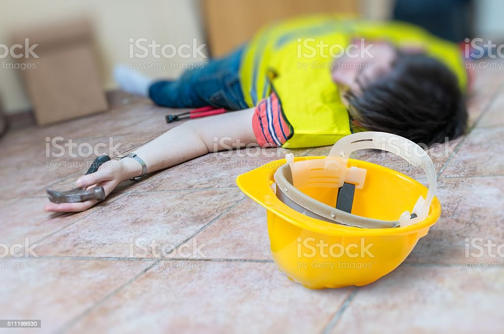 Work injury concept. Worker had accident and is lying injured stock photo