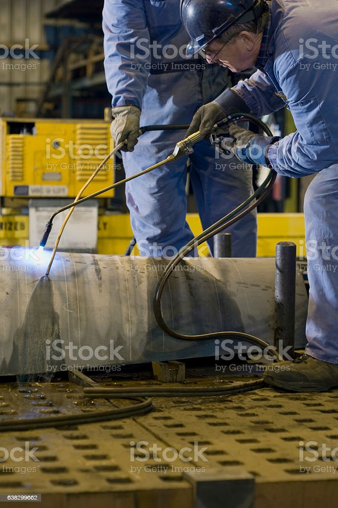 Work men welding hull of a boat in machine shop stock photo