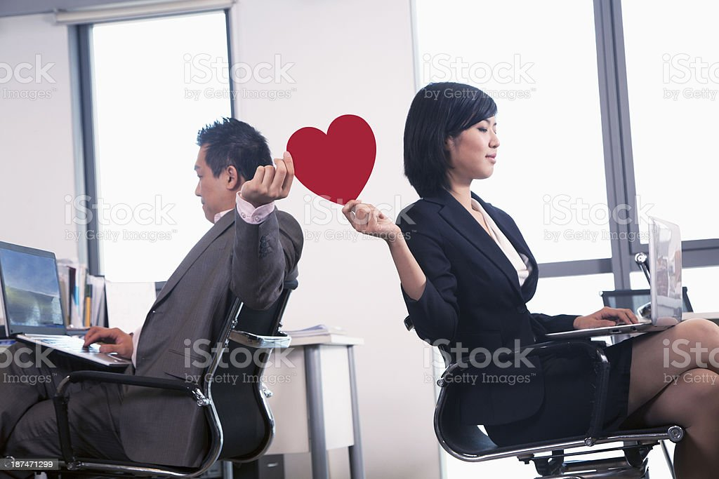 Work romance between two business people holding a heart stock photo