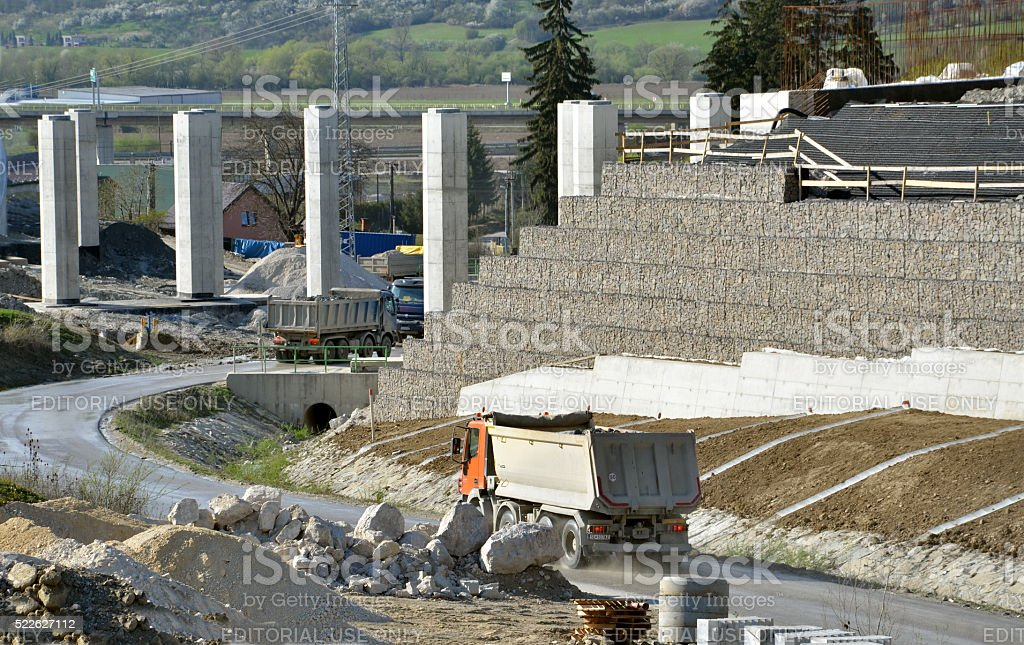 Work site with pillars, sustained wall, trucks driving on road. stock photo