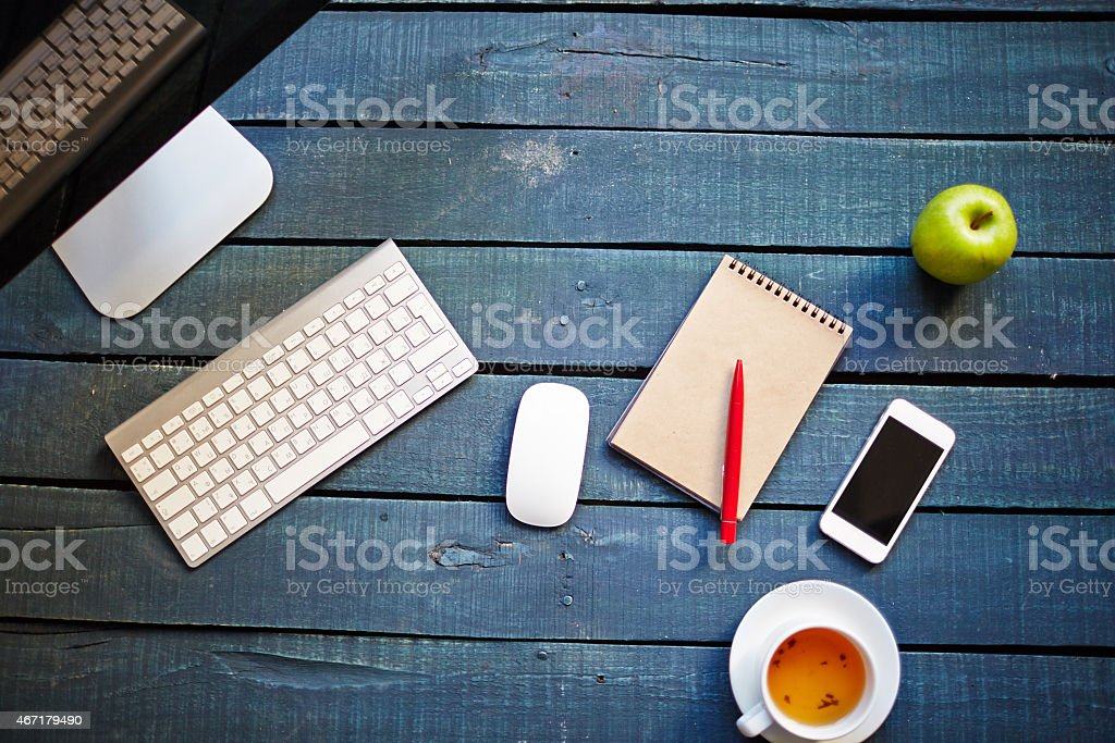 Work station on a blue tinted wooden surface stock photo