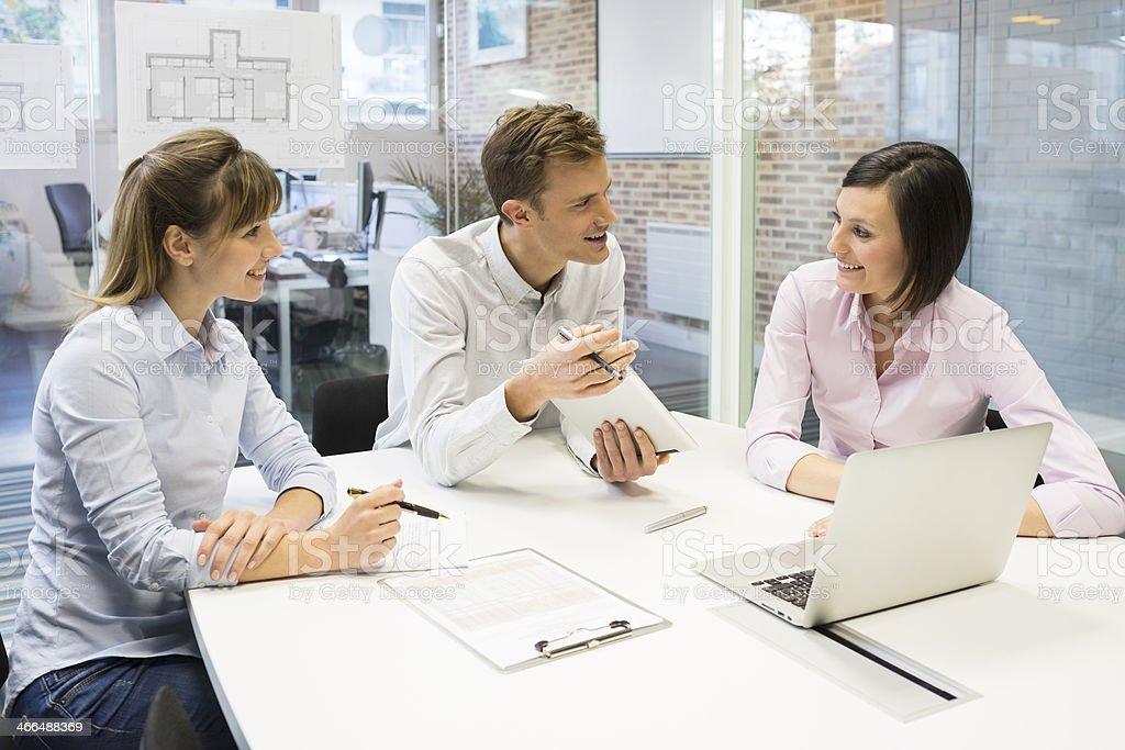 Work team in meeting room working on laptop stock photo