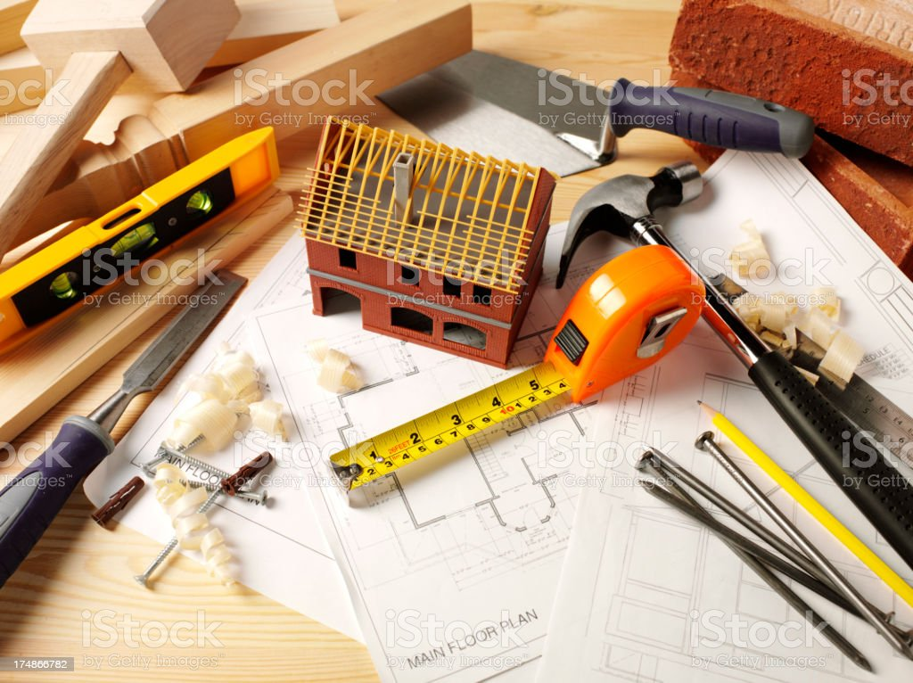 Work Tools with a Toy Model House on Paper Plans royalty-free stock photo