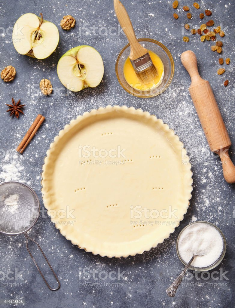 Work with the dough. Form for baking and ingredients for apple pie. The process of preparation of tart. View from above. stock photo