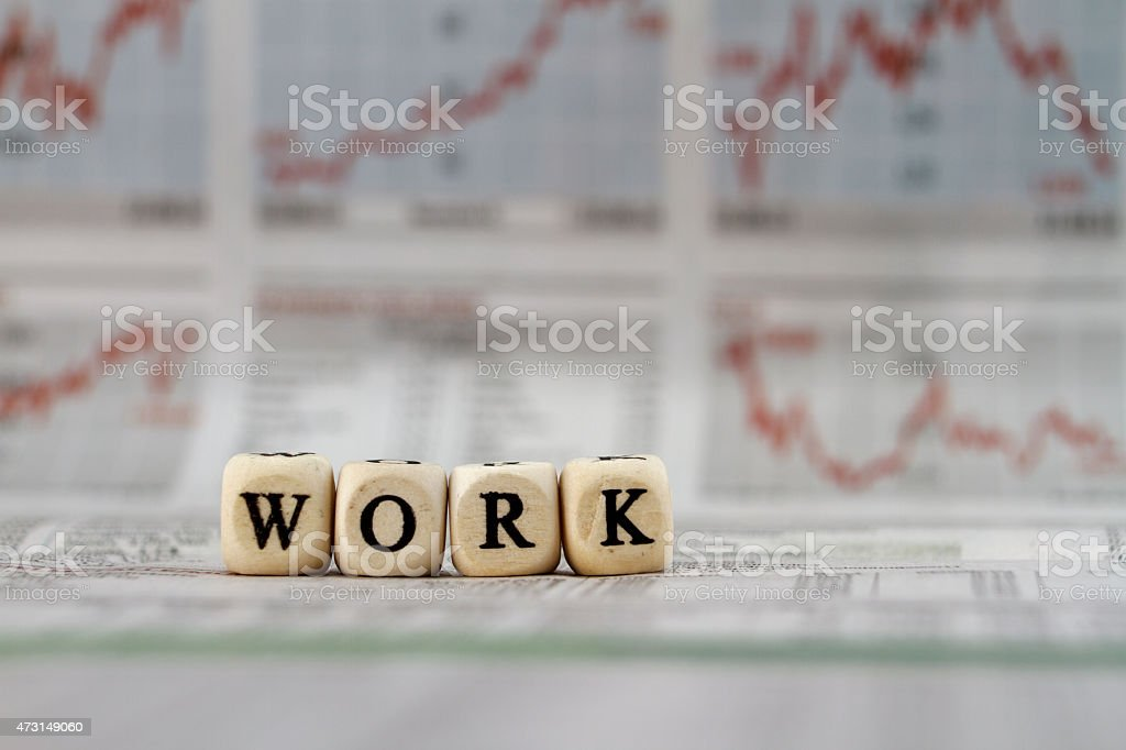 Work word built with letter cubes on newspaper background stock photo