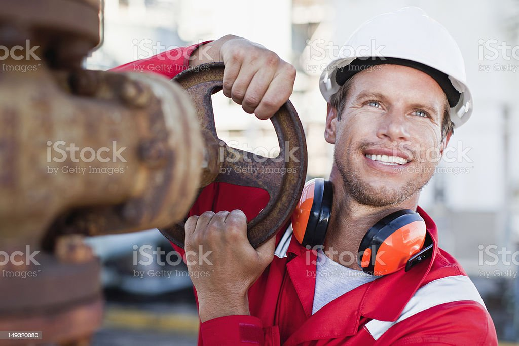 Worker adjusting gauge at chemical plant stock photo