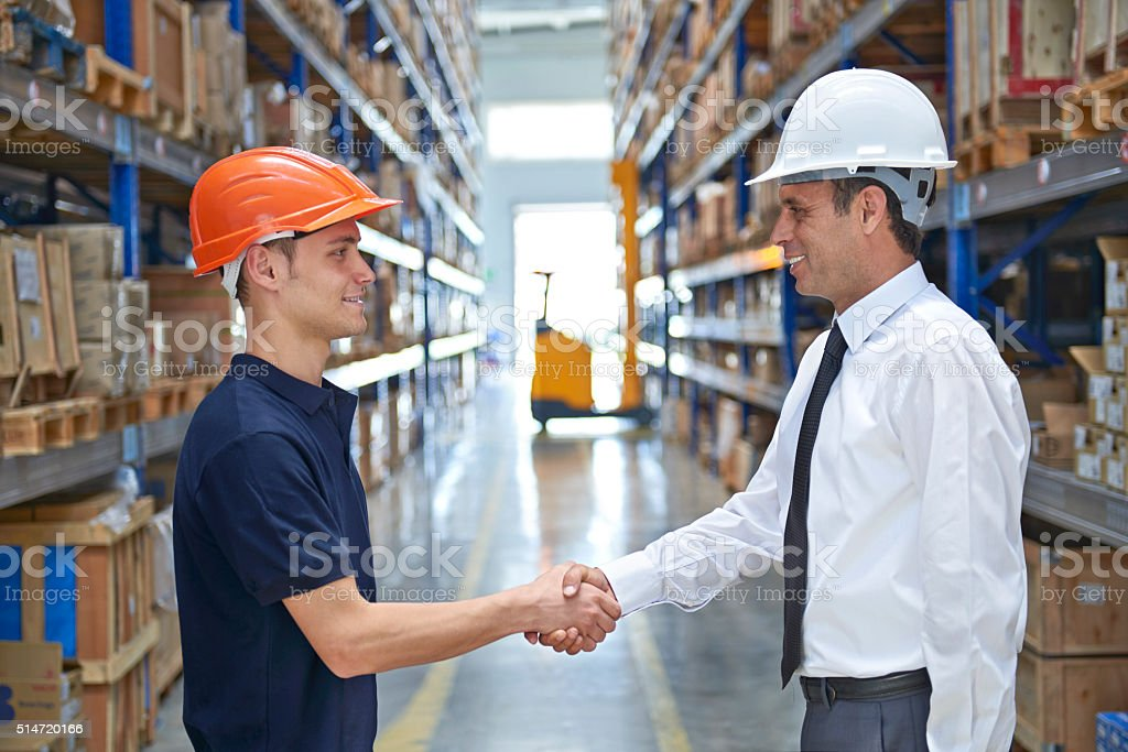 Worker and businessman shaking hands in warehouse stock photo