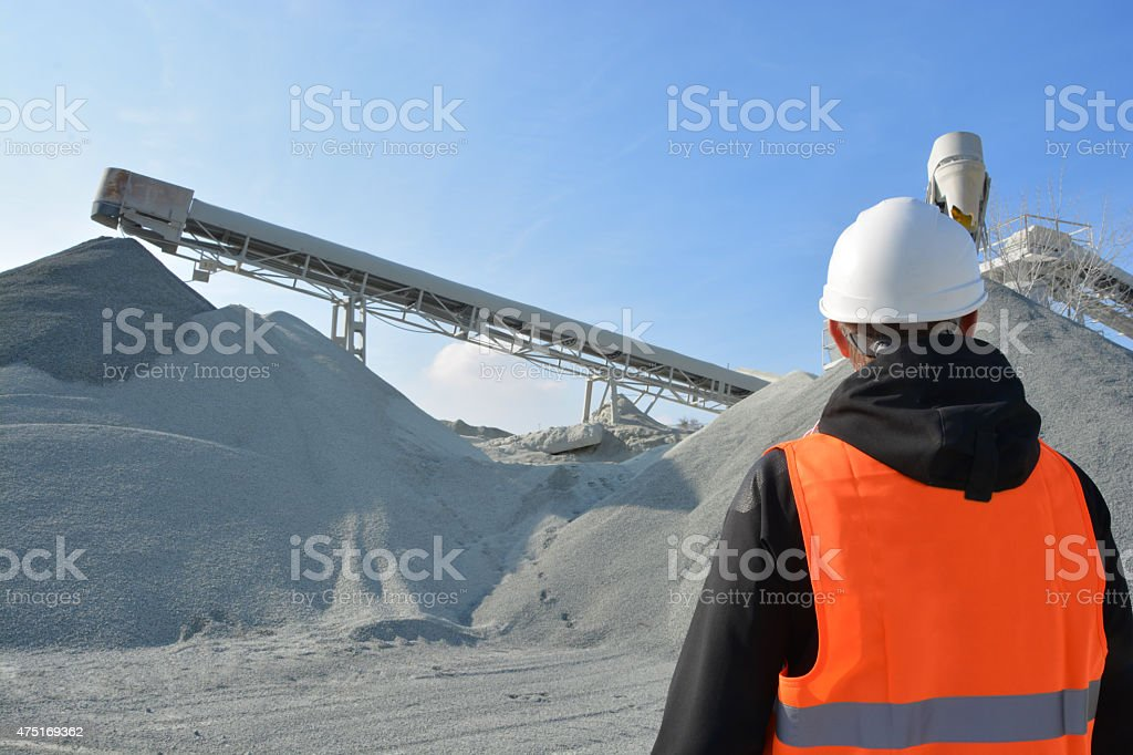 Worker and heavy machine for gravel production in background stock photo