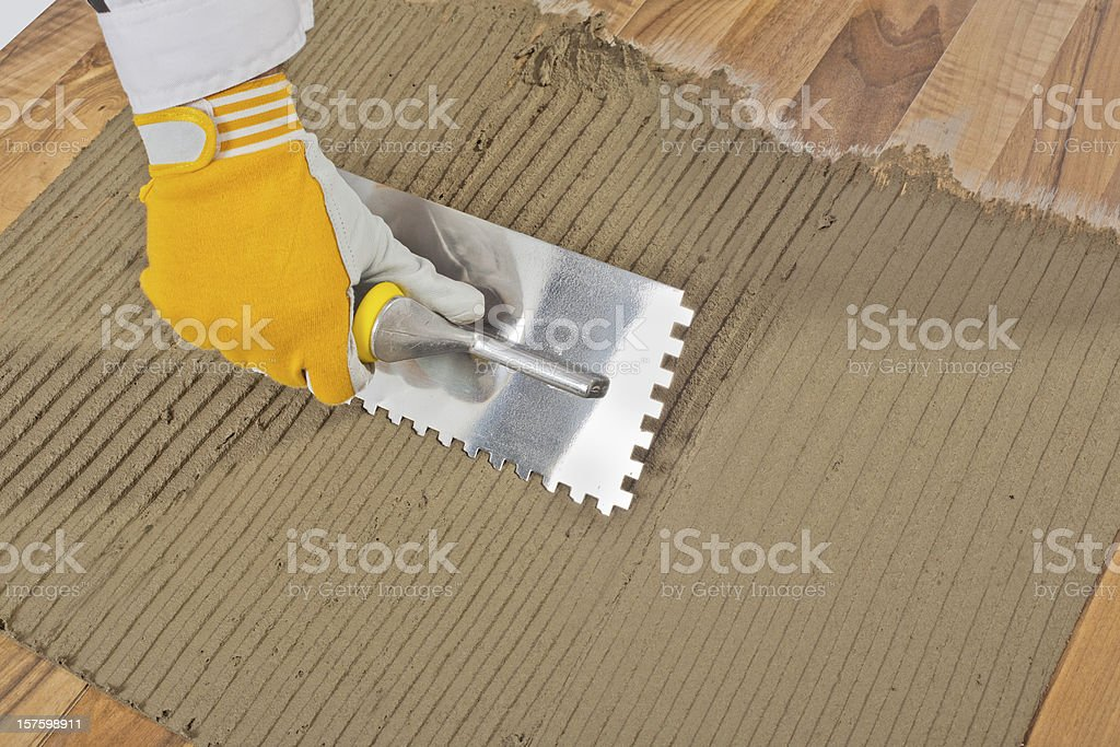 worker applied tile adhesive on old wooden floor stock photo