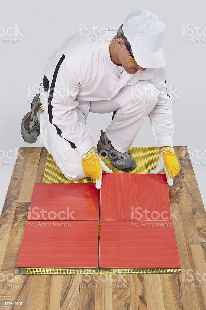 worker applies ceramic tiles on wooden floor with fiber mesh royalty-free stock photo