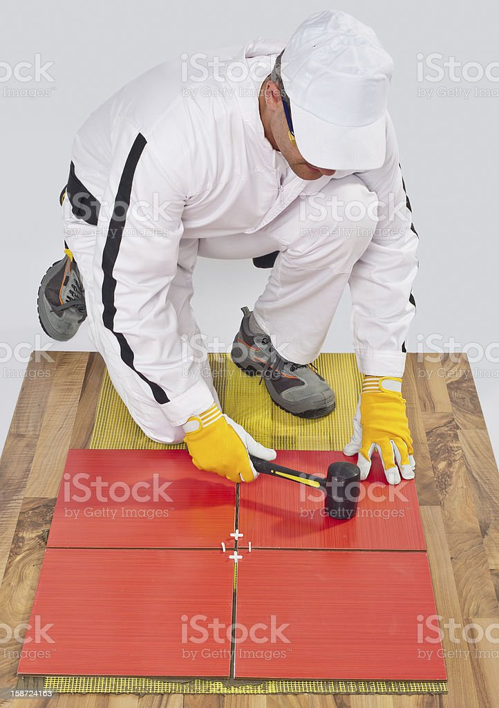 worker applies ceramic tiles on wooden floor with rubber hammer stock photo