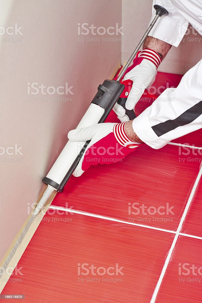 worker applies silicone sealant on corner wall tiles stock photo