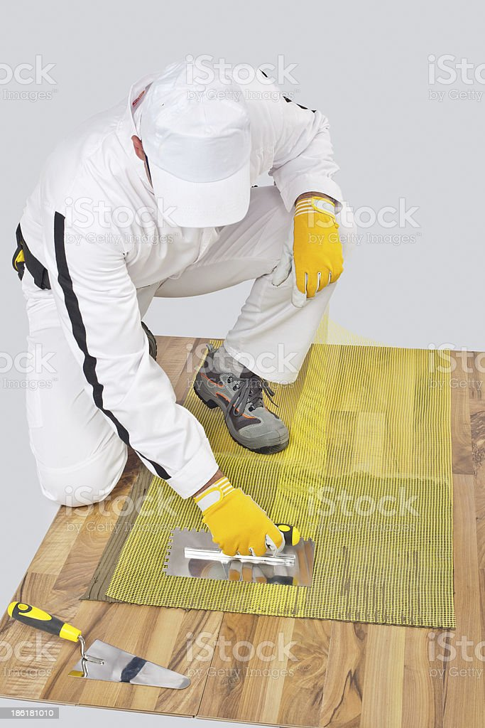 Worker applies tile adhesive on wooden floor with reinforcement stock photo