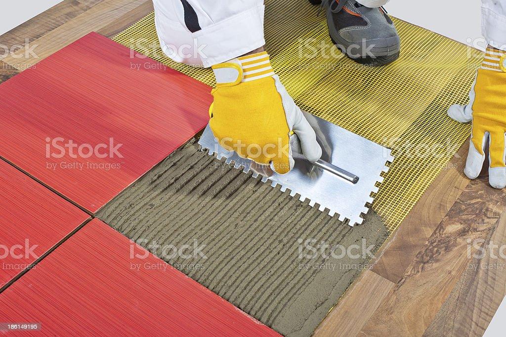 worker apply ceramic tiles on wooden floor mesh trowel stock photo