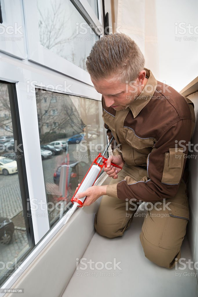 Worker Applying Glue With Silicone Gun stock photo