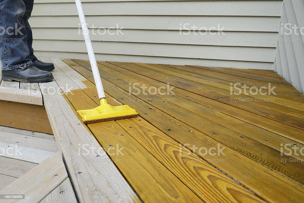 Worker Applying Stain to Deck stock photo