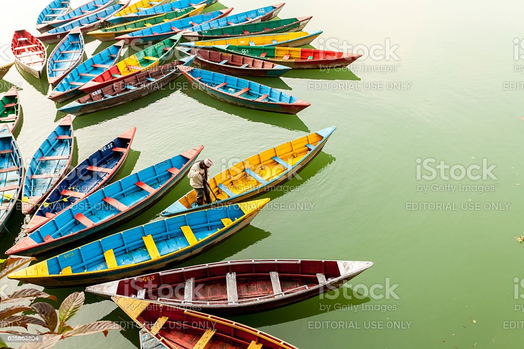 Worker are  cleaning  colorful boats on   Phewa lake, Pokhara, Nepal stock photo