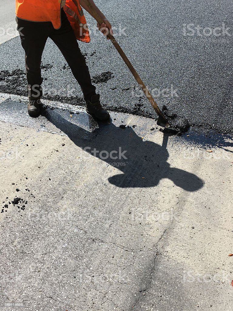 worker asphalt road in the summer stock photo