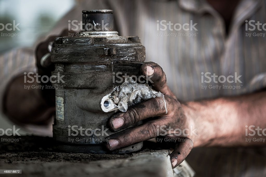 Worker at a Auto workshop cleaning the motor. stock photo