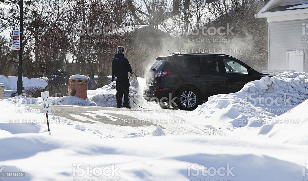 Worker at Car Wash Pre-Cleaning Vehicle in Winter stock photo