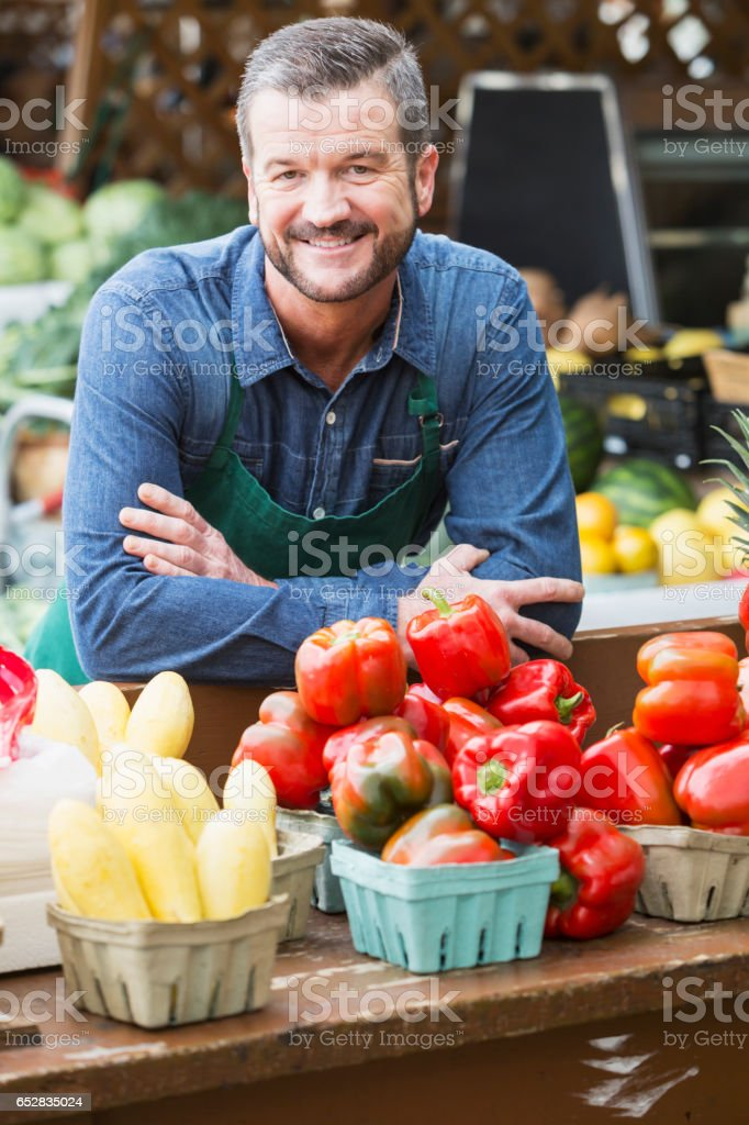 Worker at farmer's market selling fruits and vegetables stock photo