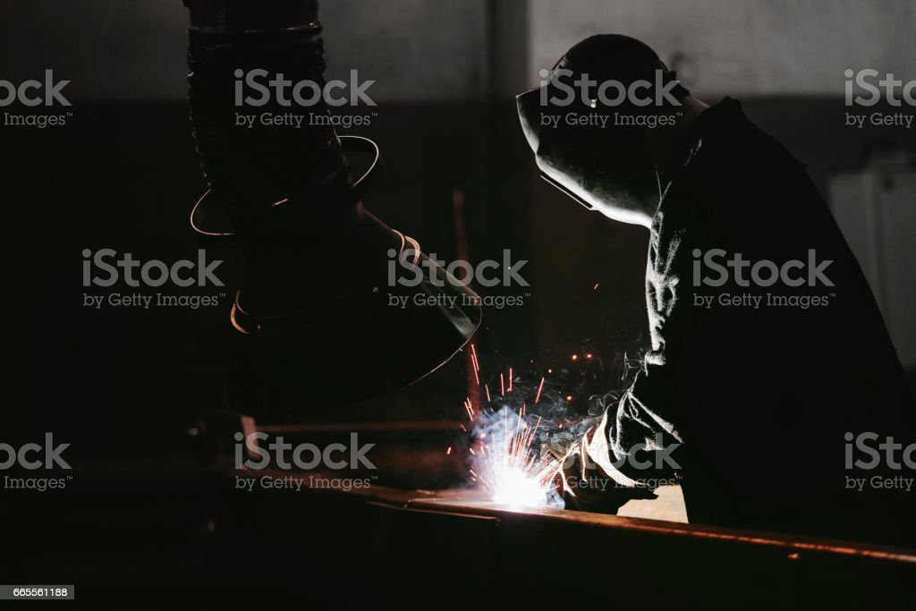 Worker at the factory in the helmet is of iron in the welding process...