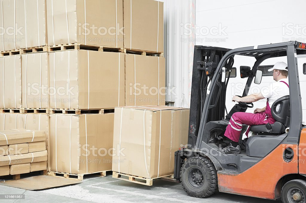 Worker at warehouse using forklift to load big boxes royalty-free stock photo