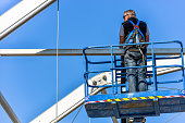 worker attaching fasteners to a beam