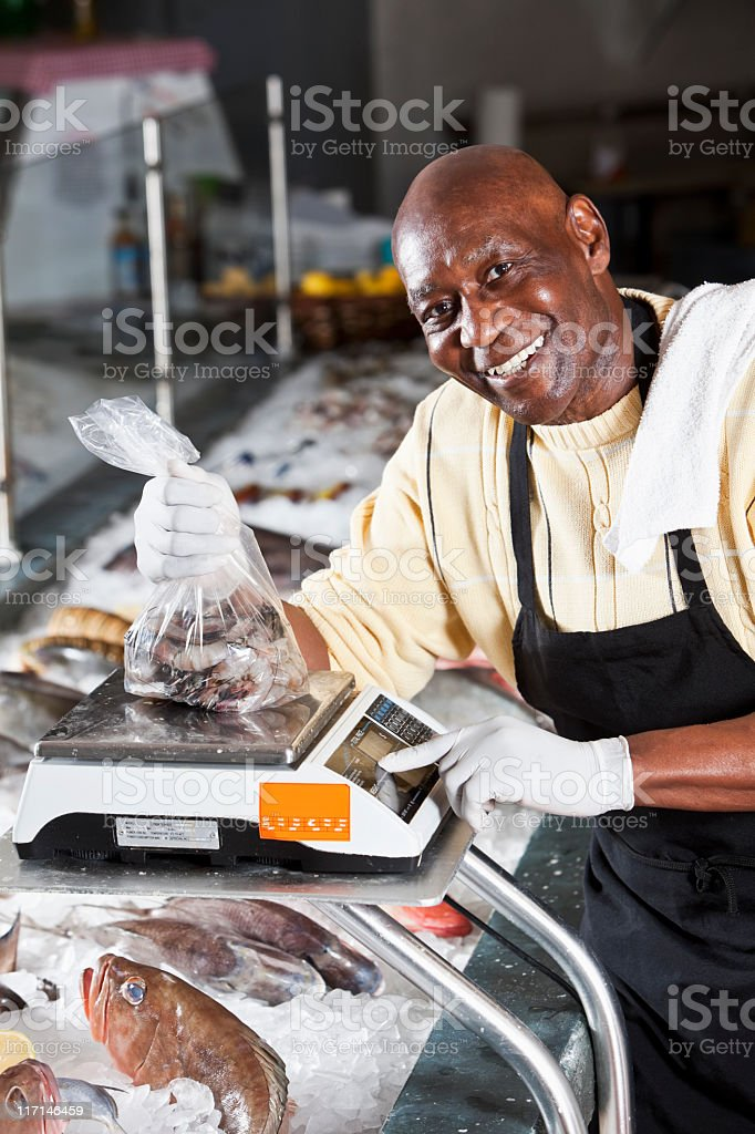 Worker behind counter in fish market stock photo