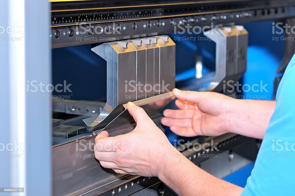 Worker bends a metal plate on the machine stock photo