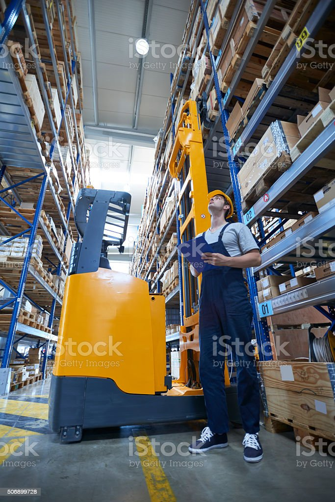 Worker beside forklift in warehouse stock photo