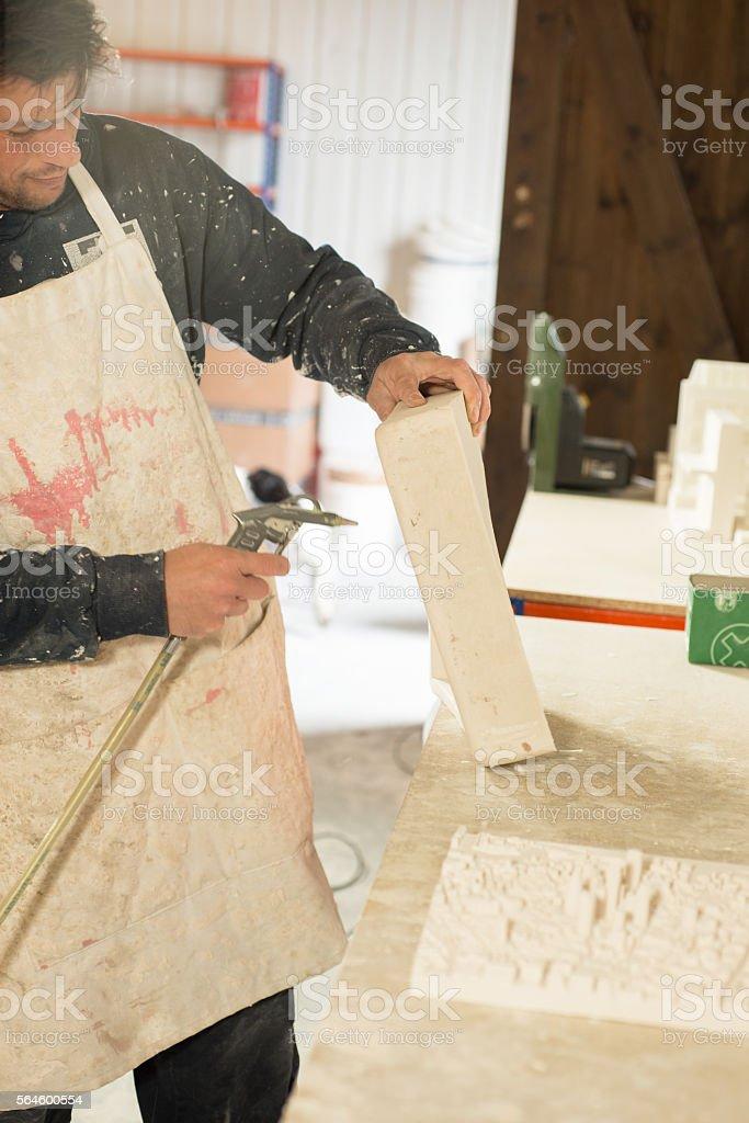 Worker Blasting Air Onto Plaster Model for Dusting stock photo