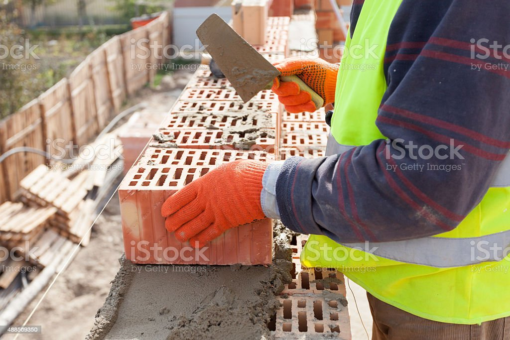 Worker bricklayer installing red brick with trowel putty knife outdoors stock photo
