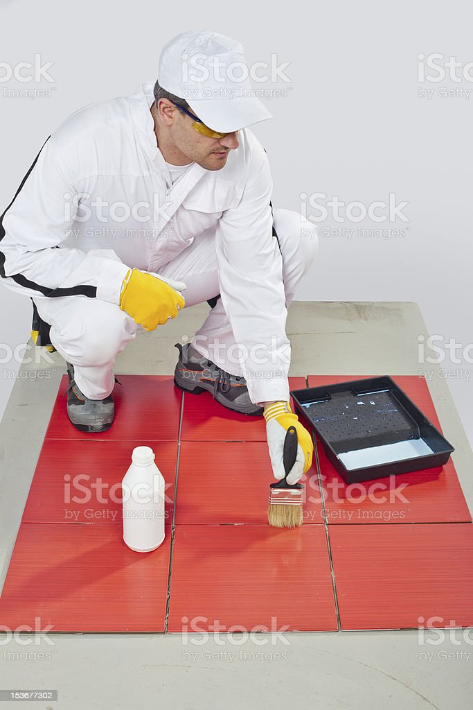 worker brush primer grout of red tiles stock photo