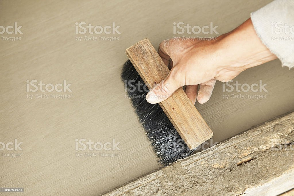 Worker Brushing Traction Lines into a Wet Concrete Floor royalty-free stock photo