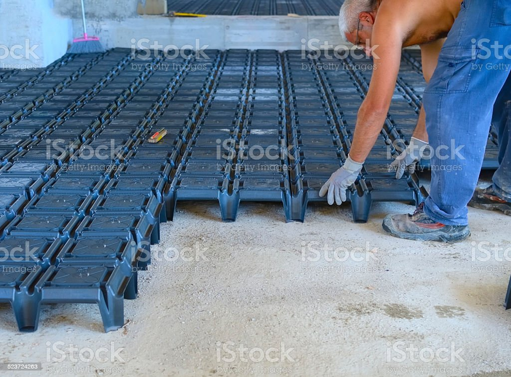 worker building ventilated crawl spaces, stock photo