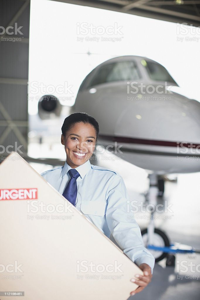 Worker carrying large box in hangar royalty-free stock photo