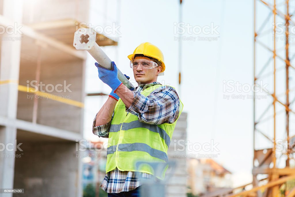 Worker carrying steel support bars on construction site stock photo