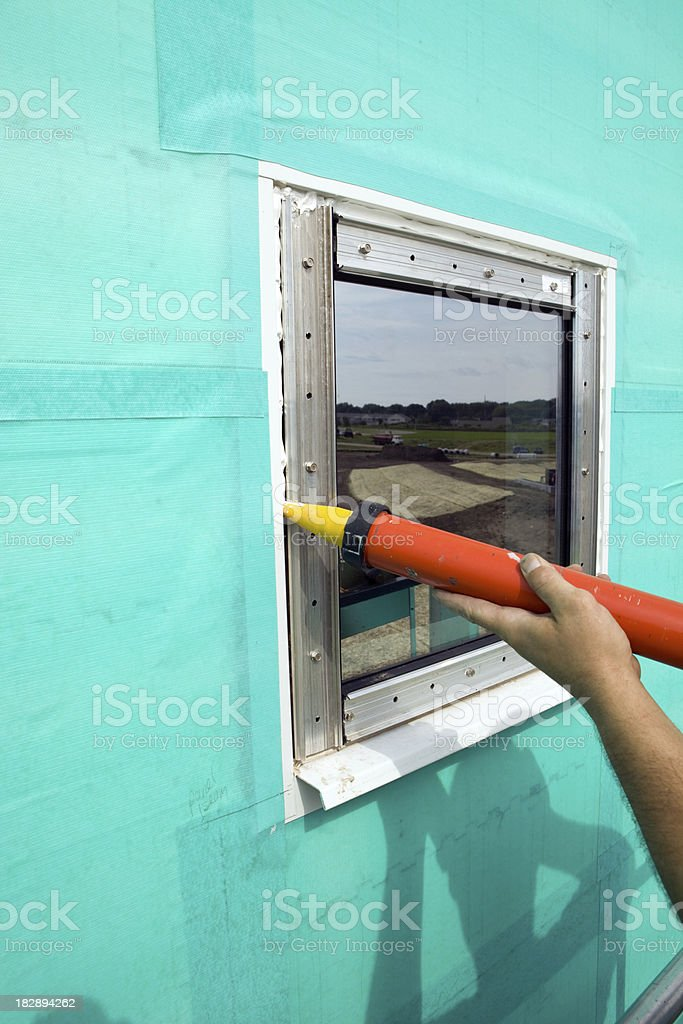 Worker Caulking Energy Efficient Commercial Window stock photo