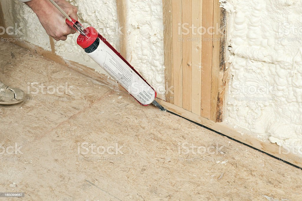 Worker Caulking Wall Plate to Subfloor stock photo
