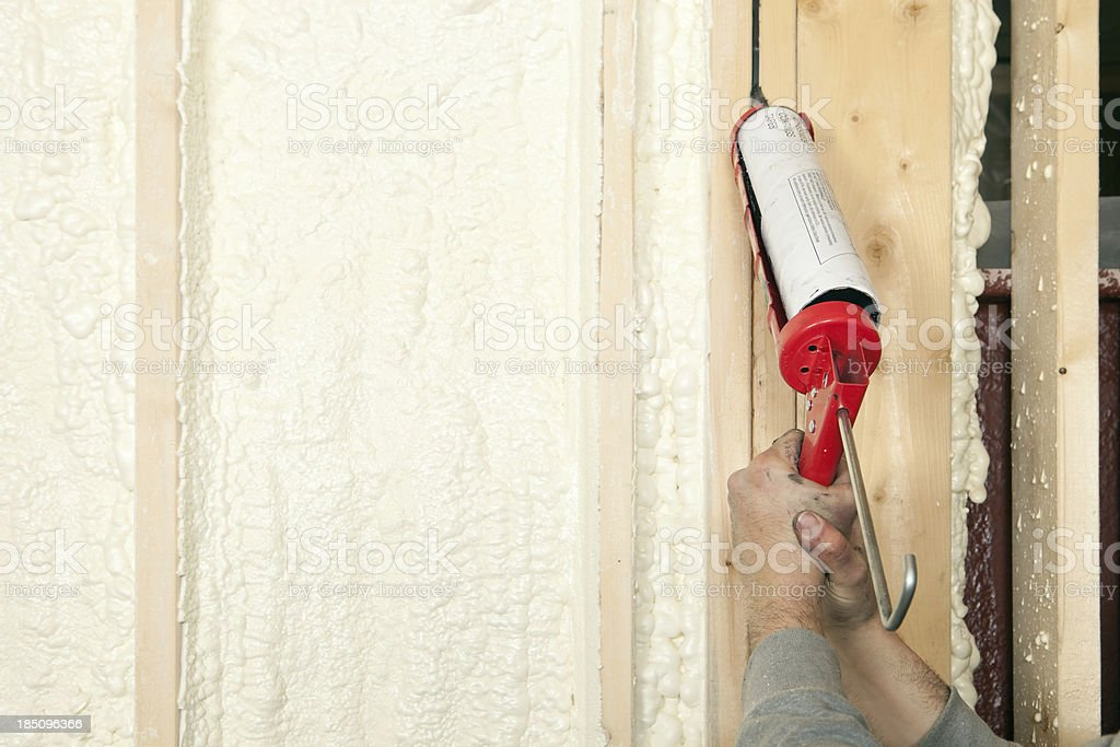 Worker Caulking Wall Studs stock photo