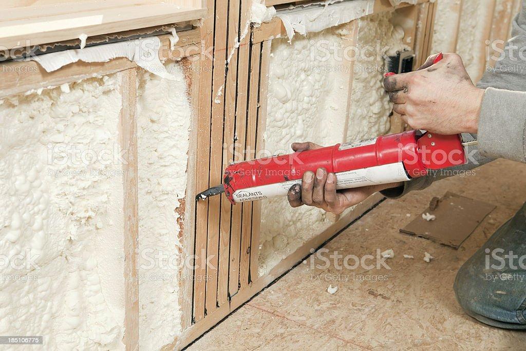 Worker Caulking Wall Studs stock photo