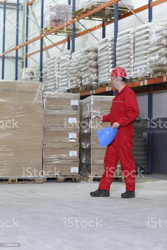 worker checking inventory stocks at a factory storeroom royalty-free stock photo