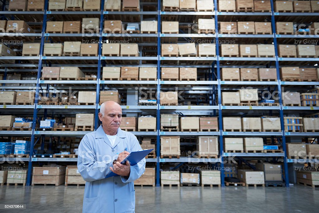 Worker checking stock in warehouse stock photo